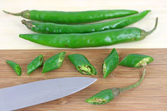 Hot peppers on wood cutting board Stock Images