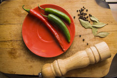 Hot peppers on wooden surface Royalty Free Stock Photos
