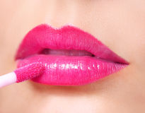 Hot Pink Lipstick. Lip Gloss On Lips And Brush Stock Photo