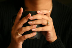 Hot piping drink. Woman holding a cup of tea/coffee/soup. Image has a shallow DOF and focus is on the fingernails. A warm tone has been given to set the mood stock image