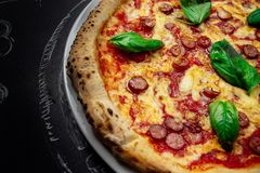 Hot pizza with cheese. Meat,  fresh basil on background Royalty Free Stock Photo