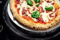 Hot pizza with cheese. Meat,  fresh basil on background Royalty Free Stock Photos