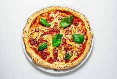 Hot pizza with cheese. Meat,  fresh basil on background Royalty Free Stock Photography