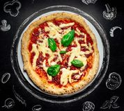 Hot pizza with cheese. Meat,  fresh basil on background Stock Images