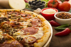Hot pizza. Fresh hot pizza ready to eat with vegetables in the background royalty free stock images