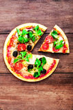 Hot pizza slice with cheese on a rustic wooden table. Ready to eat with copyspace royalty free stock image