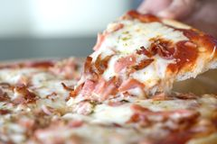 Hot pizza slice with dripping ham sausage and mozzarella cheese. Close up af a hot pizza slice with dripping ham sausage and mozzarella cheese royalty free stock photography