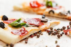 A hot pizza slice with dripping melted cheese. Isolated on white. A hot pizza slice with dripping melted cheese, with mushrooms, salami, peperoni, tomatoes stock photos
