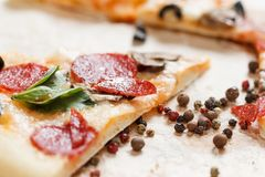A hot pizza slice with dripping melted cheese. on white. A hot pizza slice with dripping melted cheese, with mushrooms, salami, peperoni, tomatoes, basil stock image