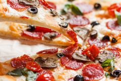 A hot pizza slice with dripping melted cheese. on white. A hot pizza slice with dripping melted cheese, with mushrooms, salami, peperoni, tomatoes, basil stock photo