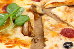 Hot pizza slice with melting cheese, mushrooms, salami and crumbs Royalty Free Stock Photos