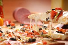 American pizza with pepperoni, mozzarella and tomato sauce. Pizza on a wooden table, morning, dawn stock photography