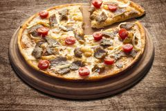 Hot pizza slice with melting cheese on a rustic wooden table. Hot pizza slice with melting cheese on a rustic wooden table stock image