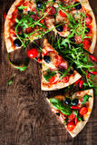 Hot pizza slice with Pepperoni, melting cheese on a rustic wooden table close up. stock image