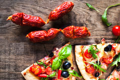 Hot pizza slice with Pepperoni, olives and cheese on a rustic wooden table close up. royalty free stock image