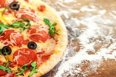 Hot pizza slice with Pepperoni, tomatoes, melting cheese on a ru. Stic wooden board royalty free stock photo