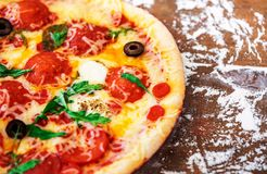 Hot pizza slice with Pepperoni, tomatoes, melting cheese on a rustic wooden table close up. Copy space Royalty Free Stock Image