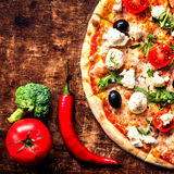 Hot pizza slice with vegetables and cheese on a rustic wooden t Royalty Free Stock Image