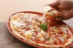 Hot pizza slice on wooden table. Pizza delicious for lunch stock photo