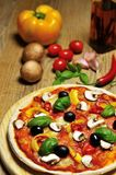 Hot pizza and some ingredients. Hot pizza on wooden board and some ingredients in the background royalty free stock photos