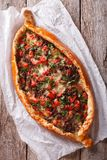 Hot pizza Turkish pide close up on the table. vertical top view Royalty Free Stock Images