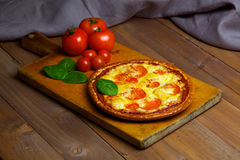 Hot pizza with vegetables on an old wooden board Stock Photo
