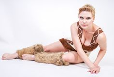 Hot plus size woman in fur carnival costume of primitive man on white background in Studio. a beautiful savage girl in a brown dre. Ss and with fur on her calves stock photos