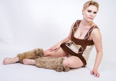 Hot plus size woman in fur carnival costume of primitive man on white background in Studio. a beautiful savage girl in a brown dre. Ss and with fur on her calves stock photography