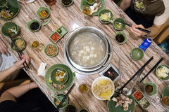Hot pot. A table and people eating a Chinese hot pot meal stock image