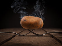 Hot potato on forks. Hot potato with big steam on two steel forks on a rustic wooden table stock photo
