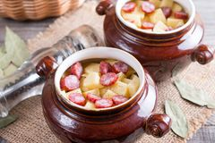 Hot potato goulash with bacon and Vienna sausages served in a ceramic bowl with on an old wooden table. Hot potato goulash with bacon and Vienna sausages served Royalty Free Stock Images