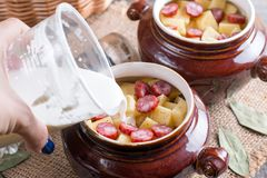 Hot potato goulash with bacon and Vienna sausages served in a ceramic bowl with on an old wooden table. Hot potato goulash with bacon and Vienna sausages served Royalty Free Stock Photos