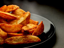 Hot potato wedges on black plate Stock Photography