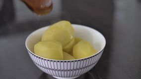 Hot potatoes in a cup. With a wood spoon stock video footage