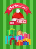 Hot Prices Xmas Sale Poster Santa Claus Hat Label. Hot prices Xmas sale poster Santa Claus hat on discount label, mountains of gift boxes on striped green Stock Photos