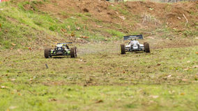 Hot pursuit. Two remote controlled models of cars on dirty race track Royalty Free Stock Photography