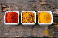 Hot red chili powder, curry and turmeric powder. On wooden background Royalty Free Stock Photography