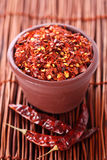 Hot Red Chilli Chillies crushed pepper in pot. Hot Red Chilli Chillies crushed pepper in teracotta pot, three whole chillies and wooden sticks on Background stock images