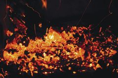 Hot red coals from firewood in a fireplace on a black background. Hot red coals from firewood in a fireplace Stock Images