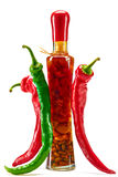 Hot red, green peppers around bottle of vegetables Royalty Free Stock Photos