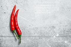 Hot red pepper in the pod. On white rustic background royalty free stock photography