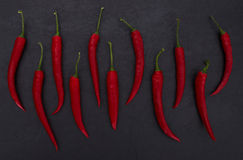 Hot red peppers on black slate background Royalty Free Stock Photos