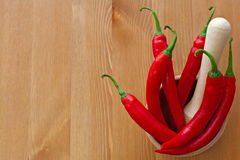 Hot red peppers and wooden pounder. On the table royalty free stock images