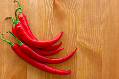 Hot red peppers on the wooden table Royalty Free Stock Photos