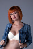 Hot redhead girl posing in seamless bra and jacket Stock Image