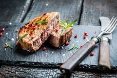 Hot roasted beef with fresh rosemary ready to eat. On burnt table Stock Photography
