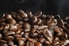 Hot roasted coffee beans. And steam on black Stock Image