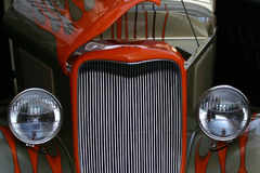 Hot Rod Eyes. Peek-a-boo look at the incredible grill, lights and flame paint of a fully remodeled classic American truck Royalty Free Stock Photography