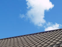 Hot roof. Dark brown roof. Blue sky background with clouds Stock Photos