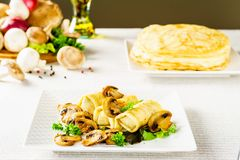 Hot Russian pancakes or blini with mushrooms. stock photography